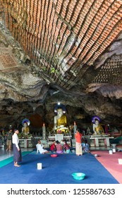 HPA-AN, MYANMAR - 19 NOVEMBER, 2018: Vertical picture of local people praying in front of Buddha Statues inside of Kaw Ka Thaung Cave, located close to Hpa-An, Myanmar