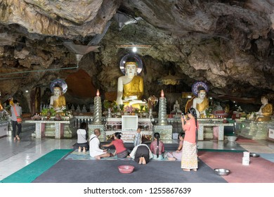 HPA-AN, MYANMAR - 19 NOVEMBER, 2018: Horizontal picture of local people praying in front of Buddha Statues inside of Kaw Ka Thaung Cave, located close to Hpa-An, Myanmar