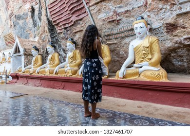 HPA-AN, MYANMAR - 19 NOVEMBER, 2018: Horizontal picture of brunette woman at the exterior of Kaw Goon Cave, landmark of Hpa-An, Myanmar