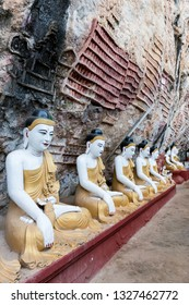 HPA-AN, MYANMAR - 19 NOVEMBER, 2018: Vertical picture of aligned Buddha statues at Kaw Goon Cave, important landmark of Hpa-An, Myanmar