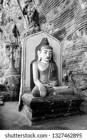 HPA-AN, MYANMAR - 19 NOVEMBER, 2018: Black and white picture of single golden Buddha statue at beautiful Kaw Goon Cave, landmark of Hpa-An, Myanmar