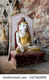 HPA-AN, MYANMAR - 19 NOVEMBER, 2018: Vertical picture of single golden Buddha statue at beautiful Kaw Goon Cave, landmark of Hpa-An, Myanmar