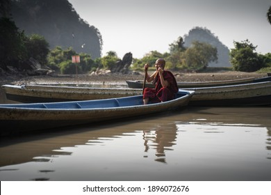 HPA-AN, MYANMAR - JANUARY 13, 2020: A monk wearing traditional robes uses his cell phone whilst sat on a wooden boat in Hpa-An, Myanmar.