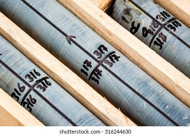 HQ diamond drill core through black shale marked up for cutting with the diamond saw and contained in wooden core boxes
