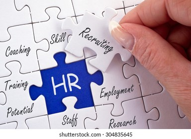 HR - Human Resources - business concept with female hand and puzzle
