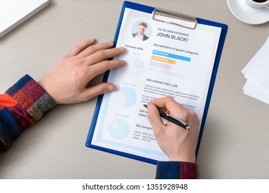 HR manager studying job resume of candidate at table