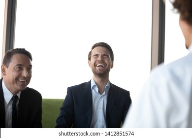 HR managers or recruiters laugh at interview with potential job candidate, joking having fun together, male applicant make good first impression on employers at hiring. Successful employment concept