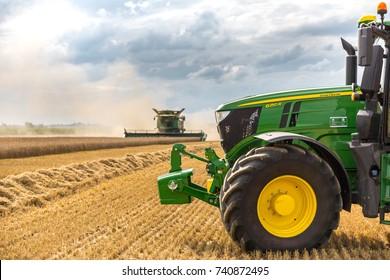 Hradec Kralove, Czechia August 4, 2017: Modern John Deere combine harvester model S685i and tractor 6250R at the harvest of wheat near the town Hradec Kralove, Northern Czechia
