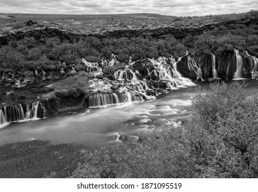 Hraunfossar Cascades, rapids and waterfalls are a unique natural wonder in Iceland with water emerging from an underground river in porous lava rock. Hot spot for tourists black and white.