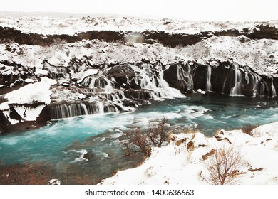 Hraunfossar Icelandic waterfalls coming out of a lava field with blue water.