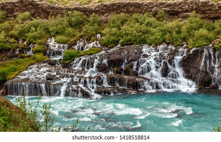 Hraunfossar waterfall powerful streams falling into Hvita river turquoise waters, Husafell, Western Iceland
