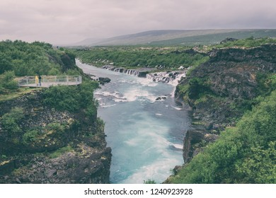 Hraunfossar waterfalls or Lava Falls, Iceland. Beautiful summer landscape, water is flowing through the lava rocks into the emerald colored Hvita river. One of the most unusual waterfalls in Iceland