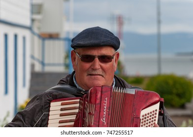 Hrisey Iceland - July 8. 2016: Old man playing red accordion during local festival