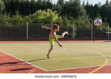 HRISTE, Czech Republic, June 6, 2017. Boy kicking soccer ball on sports field. Concept of sport, health, training, athlete. Outdoor playground for tennis, volleyball and football. Sport. Cute boy.