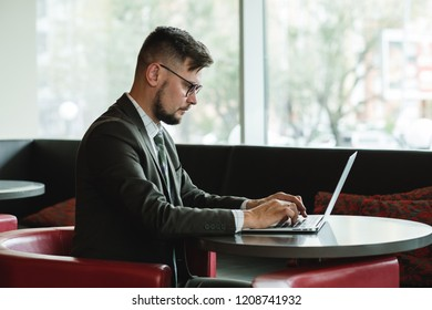Hr-manager working on laptop. Businessman in suit working on notebook computer in interior.