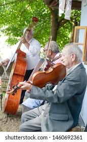 "HRUSOV, SLOVAKIA - JULY 28, 2018: ""HONTIANSKA PARADA"" Festival of Folk Art and Crafts. Fair of rustic crafts. Folk-musicians. With violin, contrabass and accordion. Central Europe. Slovak republic"