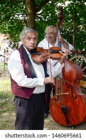 "HRUSOV, SLOVAKIA - JULY 28, 2018: ""HONTIANSKA PARADA"" Festival of Folk Art and Crafts. Fair of rustic crafts. Gipsy folk-musicians. With violin and contrabass Central Europe. Slovak republic"