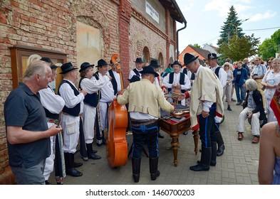 "HRUSOV, SLOVAKIA - JULY 28, 2018: ""HONTIANSKA PARADA"" Festival of Folk Art and Crafts. Fair of traditional rustic crafts. Folk-musicians are preparing for presentation. Central Europe. Slovak republic"