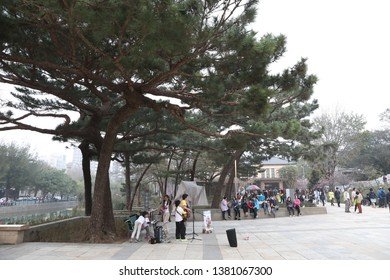 Hsinchu, Taiwan - March 2, 2019: The street artist performs/sing in Hsinchu Park by a beautiful lake.