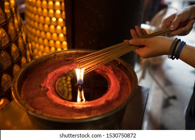 Hsinchu / Taiwan – September 16, 2019: Taiwanese woman lighting incense sticks with a flame fed by oil inside Chenghuang Taoist temple