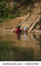 HSIPAW, MYANMAR - FEB 20, 2015 - Woman washing clothes in the Dokthawaddy River, near Hsipaw, Myanmar (Burma)