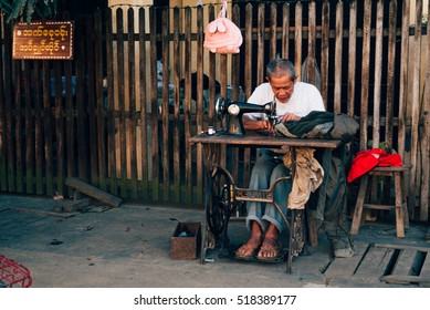 Hsipaw, Shan State, Myanmar - December 4, 2013: A way of life in rural Myanmar - A man tailor sewing cloth at his outdoor tailoring stall.