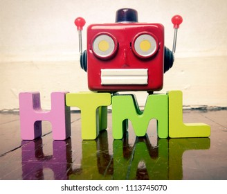 HTML wit wooden letters and a red robot talking head on a wooden floor with reflection