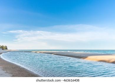Hua Hin Thailand beach, Summer sea beach with waves, blue sunny sky and white sand. Sunshine on sea wave. Sea waves near beach. Tropical sea beach. Sea wave