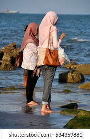 Hua Hin, Thailand - December 29, 2009:  Two Muslim women wearing traditional hajib head scarves wading in the warm ocean waters at Hua Hin beach