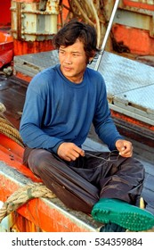 Hua Hin, Thailand - December 30, 2009:  Thai fisherman on his boat docked at the Hua Hin fishing pier mending nets used during a day at sea