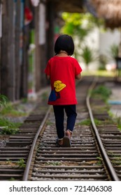 Hua Hin, Thailand - November 14, 2014: A little girl walks along railway tracks in the shadow at a hot summer day.