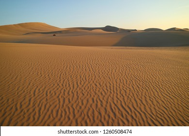 Huacachina desert with beautiful sand ripples and a dune buggy in the distance, Ica, Peru, South America