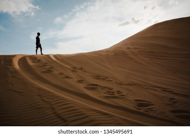 Huacachina  February 2019  A guy standing on the top of a sand dune in the Huacachina desert