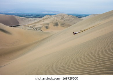 HUACACHINA, ICA, PERU - FEBRUARY 06: Unidentified sandboarder speeds down the sand dunes of Ica desert on February 06, 2010 in Ica, Peru.