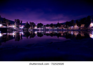 Huacachina oasis at night, the reflection of the town in the water.
