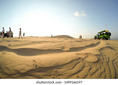 Huacachina, Peru - Apr 9, 2017: Buggy tour in the desert at sunset, people taking photos of sand dunes and sand-hills. Extreme sports, adventure, journey and travel concept. Wide angle shot.