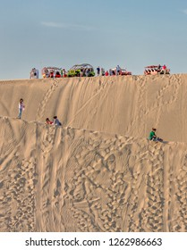 HUACACHINA, PERU - DECEMBER 29, 2013: Tourists ride the sandboards from the tops of the dunes near the Huacacina oasis