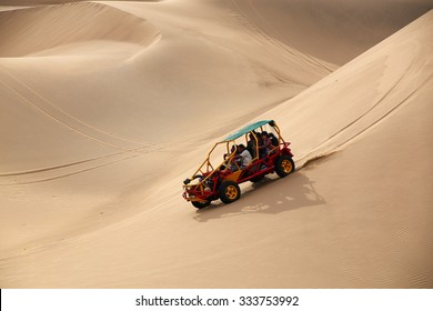 HUACACHINA, PERU - JANUARY 23: Unidentified people ride in dune buggy (blurred motion) on January 23, 2015 near Huacachina, Peru. This area attracts tourists interested in sandboarding and buggy rides