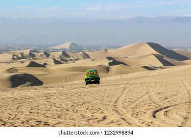 Huacachina, Peru - July 2018: Sand dunes in the Huacachina desert oasis with a dune buggy in the background. July 26, 2018.