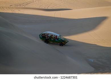 HUACACHINA, PERU - JUNE 1, 2015: Tourists on sand dune buggy trip to the dunes in Huacachina desert, Peru