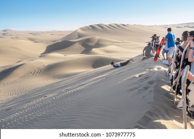 Huacachina, Peru - Oct 2, 2017: Tourists are joining the most famous tour, the sandboarding.