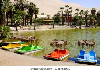 HUACACHINA, PERU - OCTOBER 16, 2017: Paddle boats available for tourists at the shore of Huacachina Oasis Lake in Ica, Peru.