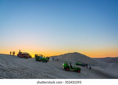 HUACACHINA, PERU - OCTOBER 27: Dune buggies and tourists on the dunes above Huacachina, Peru on October 27, 2014