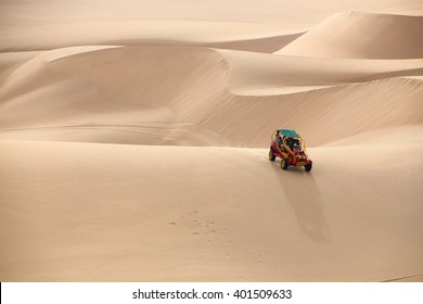 HUACACHINA, PERU-JANUARY 23: Unidentified people ride in dune buggy (blurred motion) on January 23, 2015 near Huacachina, Peru. Huacachina attracts tourists interested in sandboarding and buggy rides