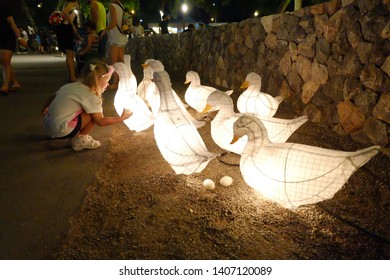 Huahin, Thailand - Circa September 2017 A little girl picks egg for looking. Duck lamps and eggs used to decorate walkway at Cicada night market Huahin.
