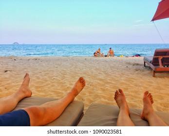 HUAHIN , THAILAND -  January 20, 2018 : Tan Feet of a couple on lounge chairs on the beach