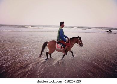 HUAHIN, THAILAND - MARCH 12, 2016: An unidentified man is riding a horse at Huahin beach of Thailand.