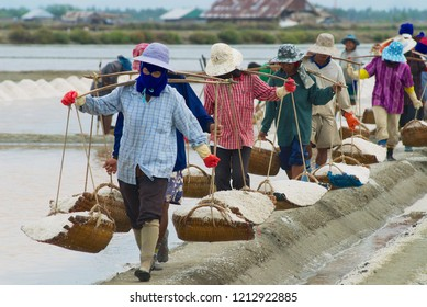 Huahin, Thailand - May 13, 2008: Unidentified people carry salt at the salt farm in Huahin, Thailand. Salt production in Huahin area brings modest income to many local families.