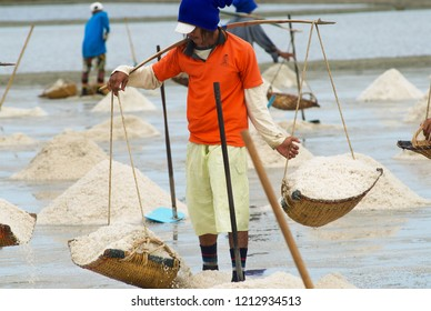 Huahin, Thailand - May 13, 2008: Unidentified man carries salt at the salt farm in Huahin, Thailand. Salt production in Huahin area brings modest income to many local families.