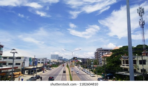 Huahin, Thailand- May 8, 2018: The beautiful blue sky and white clouds with all buildings on two sides of the roads and mountains at the farthest point.  Popular tourist spot in Thailand named Huahin.